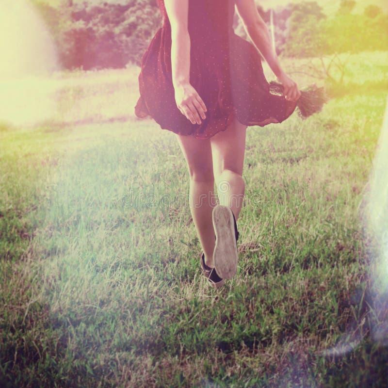 A corrida da jovem mulher através do campo para trás disparou no dia de verão do corpo inferior imagens de stock