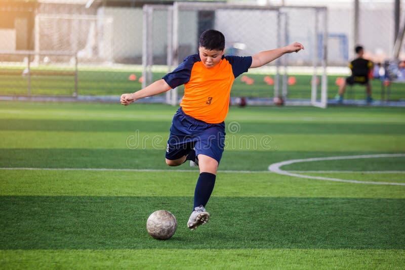 Corrida da velocidade do jogador de futebol para disparar na bola ao objetivo no relvado artificial foto de stock royalty free
