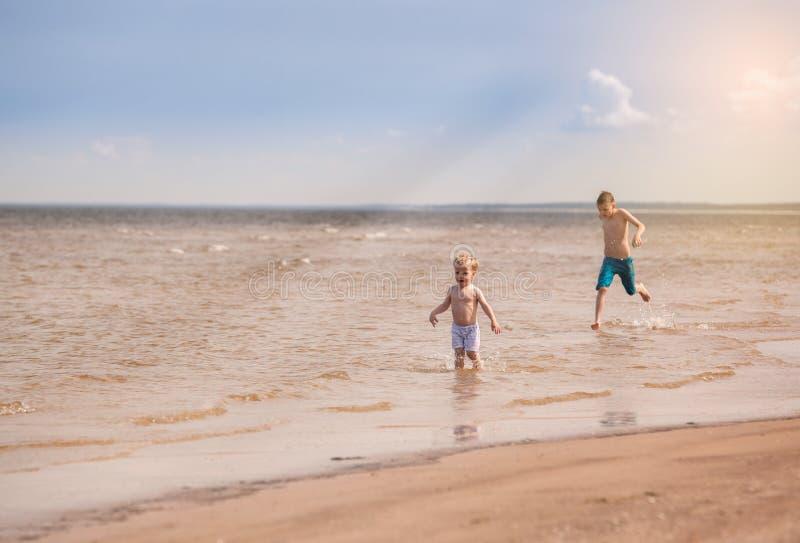 A corrida das crianças ao longo da praia e salpica com a água foto de stock