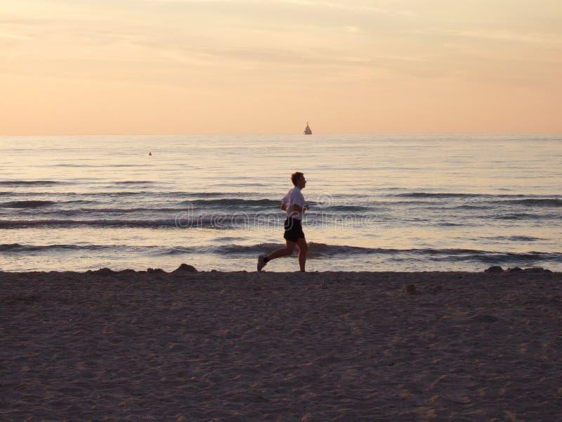 Corrida de la playa de la madrugada foto de archivo
