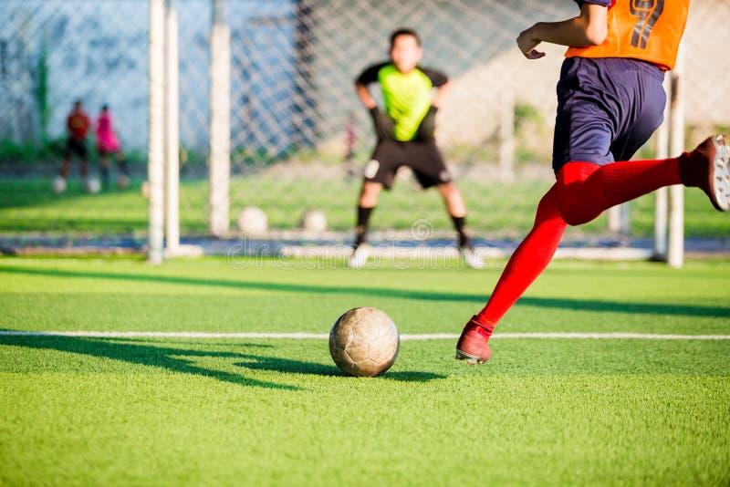 Corrida do jogador de futebol para disparar na bola no pontapé de grande penalidade ao objetivo com fundo obscuro do goleiros imagens de stock royalty free