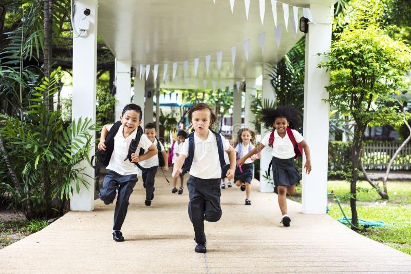 Corrida dos estudantes do jardim de infância alegre após a escola foto de stock