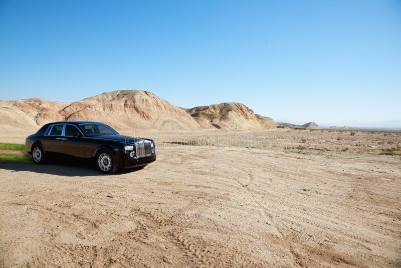 Corrida eco-amigável preta do carro de Rolls Royce fora de estrada na estrada unpaved imagens de stock royalty free