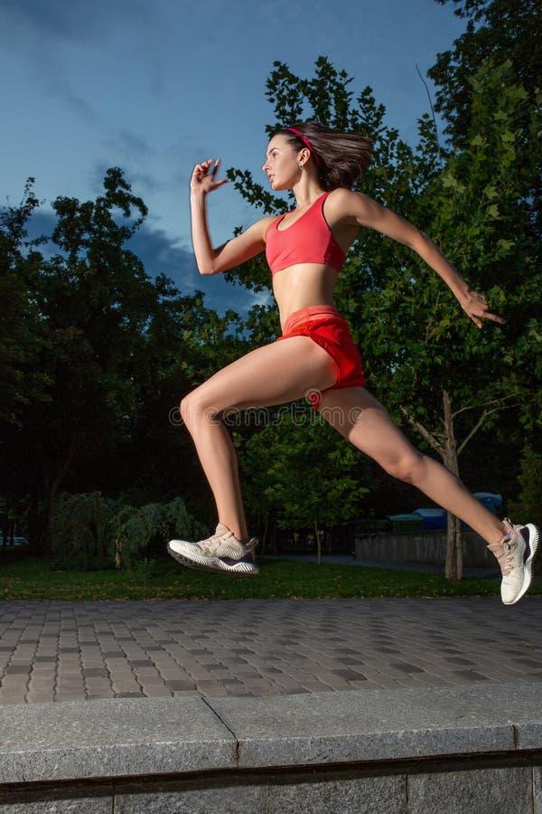 Corrida feliz nova da mulher exterior em um parque da cidade Corredor de corrida da menina na natureza para perder o peso e mante imagens de stock