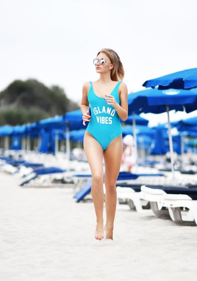 Corrida movimentando-se da menina loura bonita nova na praia tropical na veste azul do corpo e em óculos de sol redondos imagens de stock