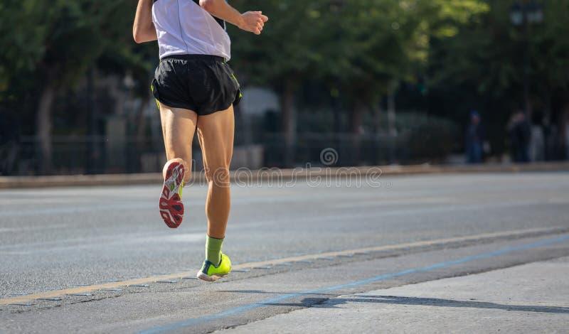 Corrida nas estradas de cidade Corredor do homem novo, vista traseira, fundo do borrão, espaço da cópia foto de stock