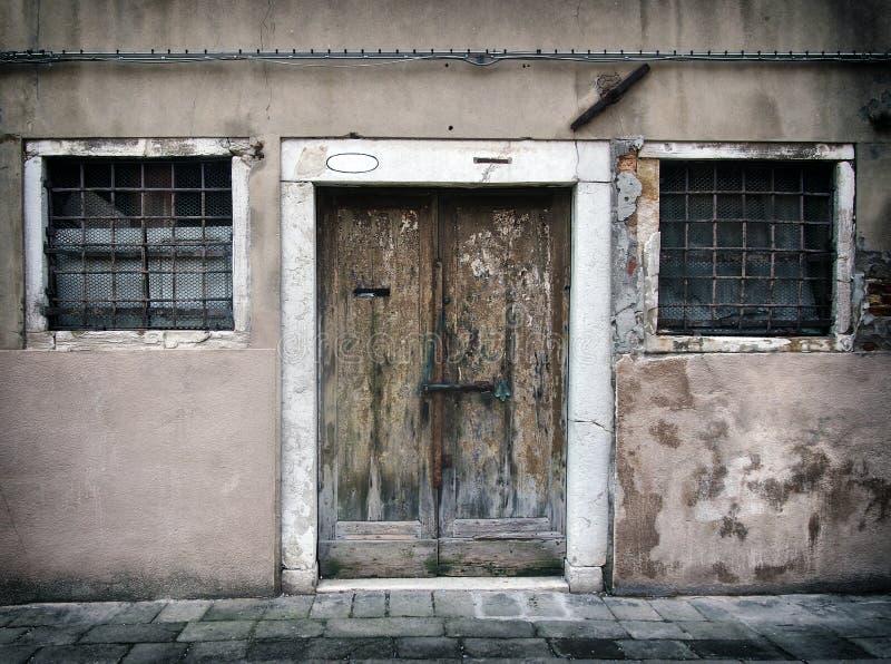 Corrida velha desvanecida abaixo da casa vazia em Veneza com paredes rachadas e aparafusada descascando a porta de madeira com as imagem de stock royalty free