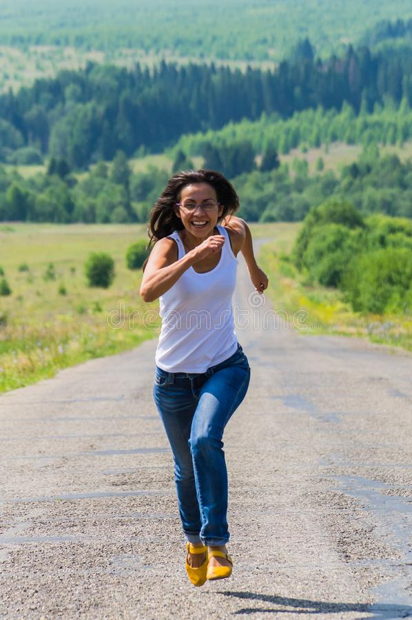 Corridas alegres da menina ao longo da estrada para imagem de stock