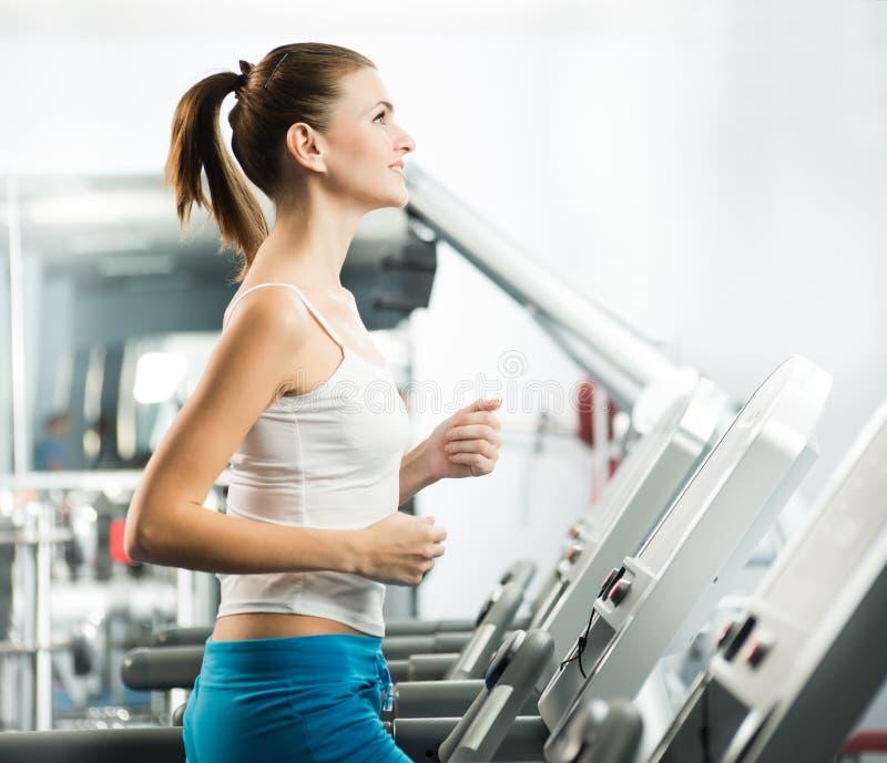 Corridas atrativas da jovem mulher em uma escada rolante fotos de stock royalty free