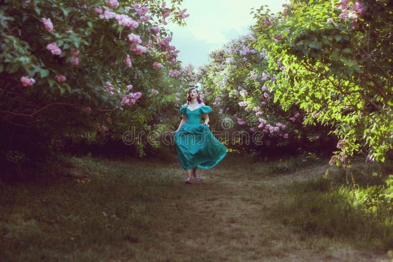Corridas da mulher através do jardim fotografia de stock royalty free