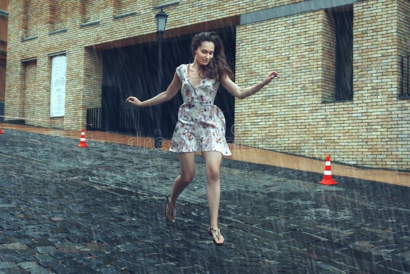 Corridas da mulher na estrada na chuva do verão fotos de stock royalty free