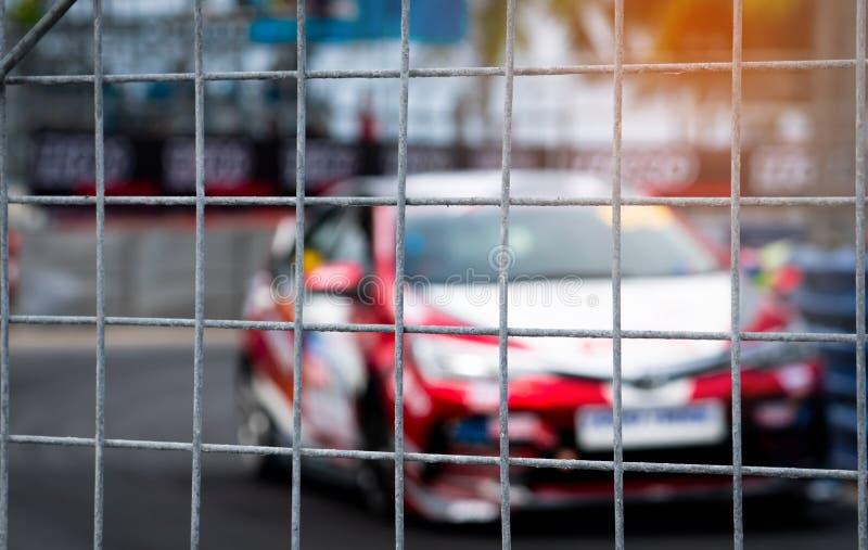 Corridas de carros do Motorsport na estrada asfaltada Vista da rede da malha da cerca no carro borrado no fundo da pista Carro de imagens de stock