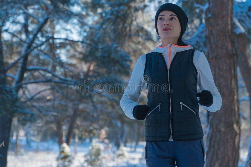 Corridas de corrida de corrida da menina da neve do inverno através das madeiras no inverno do esporte de inverno Estilo de vida  fotos de stock