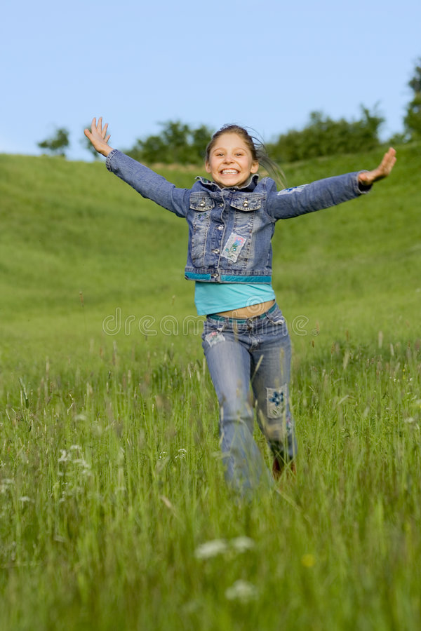 Corridas de la muchacha en una hierba fotos de archivo libres de regalías