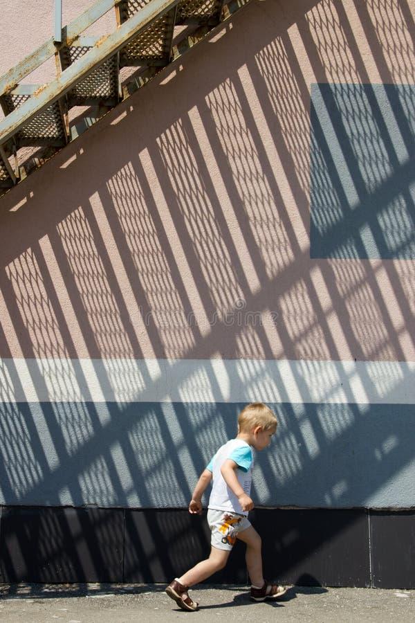 corridas del muchacho bajo las escaleras imagen de archivo