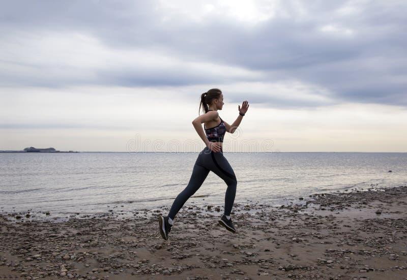 Corridas desportivas delgadas da menina ao longo da praia no por do sol imagem de stock