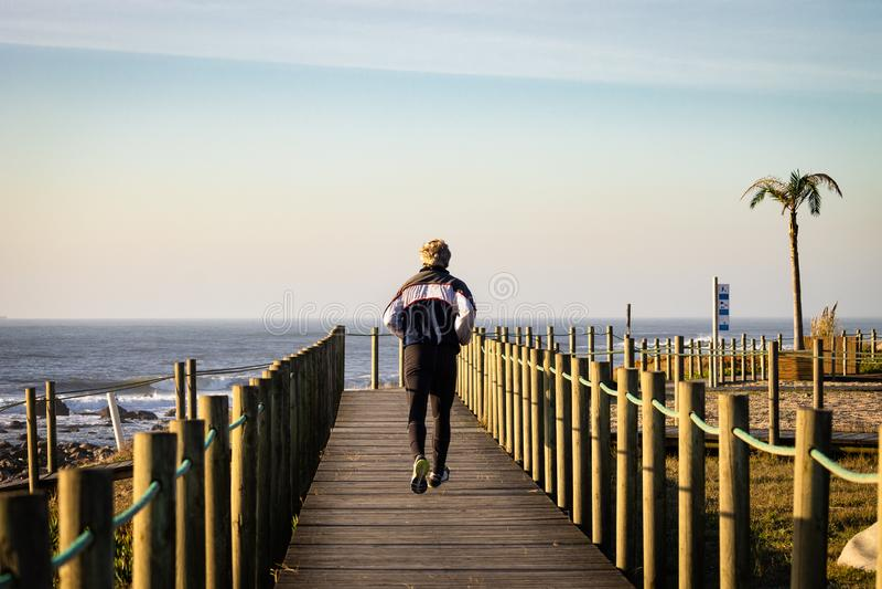Corridas do homem no passeio à beira mar fotografia de stock