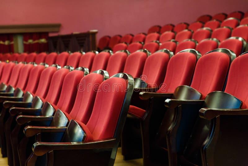 Corridoio del teatro per gli ospiti con le belle sedie delle sedie Borgogna-rosse del velluto prima della manifestazione immagini stock