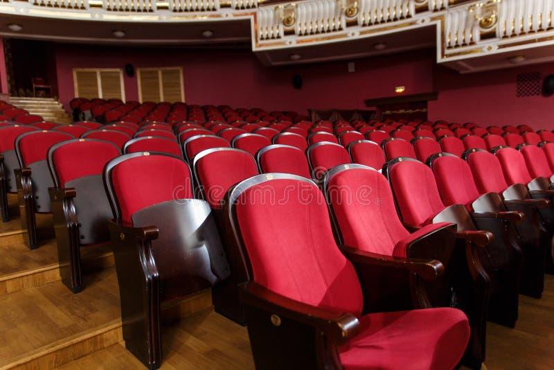 Corridoio del teatro per gli ospiti con le belle sedie delle sedie Borgogna-rosse del velluto prima della manifestazione fotografia stock