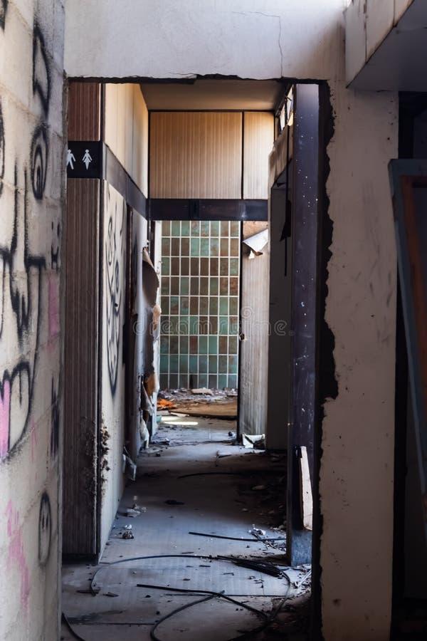 Corridoio di costruzione commerciale abbandonato con gli indicatori della toilette a sinistra - immagine fotografie stock