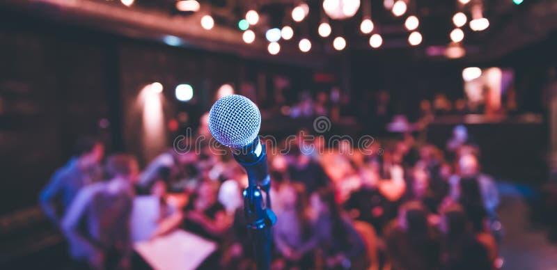 Corridoio di evento: Chiuda su del supporto del microfono, sedili con il pubblico nei precedenti confusi fotografia stock