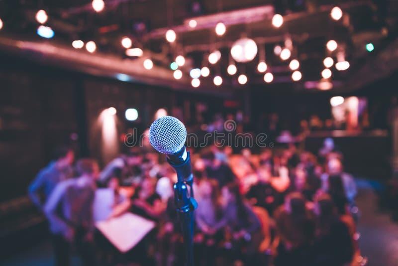 Corridoio di evento: Chiuda su del supporto del microfono, sedili con il pubblico nei precedenti confusi immagini stock libere da diritti