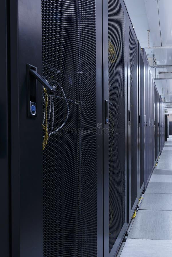Corridoio lungo nella stanza del server con le file di hardware nel grande centro dati fotografie stock