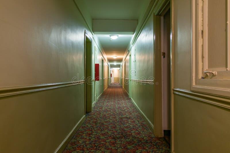 Corridoio scuro e terrificante lungo in una vecchia costruzione di appartamento americana fotografia stock libera da diritti