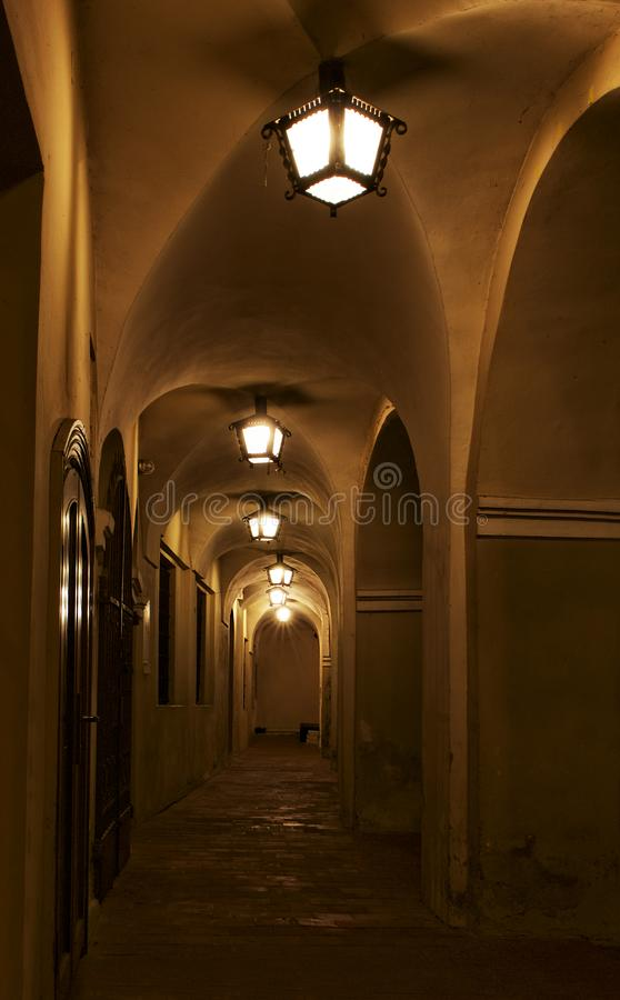 Corridor with columns in night time, abstract architectural photo, columns, diagonal, street photography. Architectural details. V. Ilnius old town. Arch royalty free stock photos
