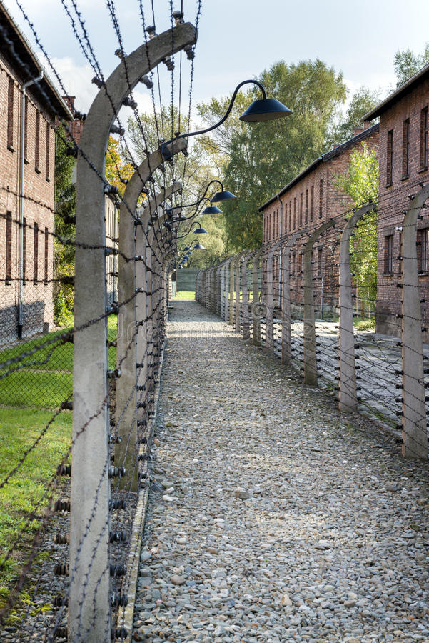 Corridor of electrified barbed-wire fences in Auschwitz II-Birkenau extermination camp. BRZEZINKA, POLAND - OCTOBER 13, 2012: Corridor of electrified barbed-wire stock photo