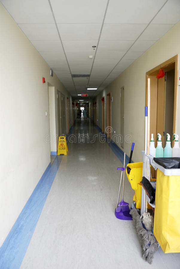 Corridor in a hospital. The corridor in a hospital with sickroom in both sides, and also a cart full of cleaning equipment by the door royalty free stock photos