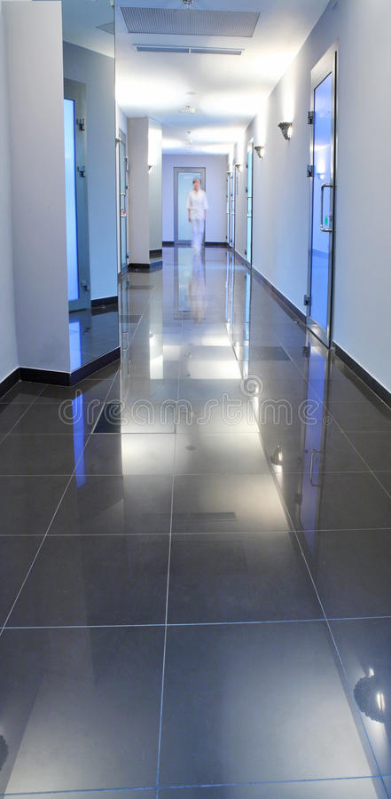 Corridor in a hospital building. With the doctor or nurse at the end royalty free stock photo