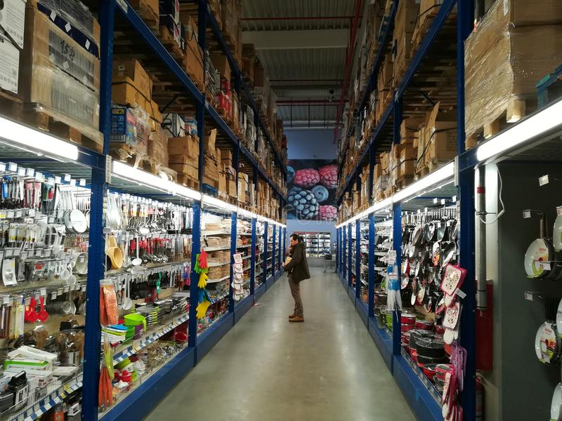 Corridor inside the hypermarket Selgros. Man looks at shelf products stock image
