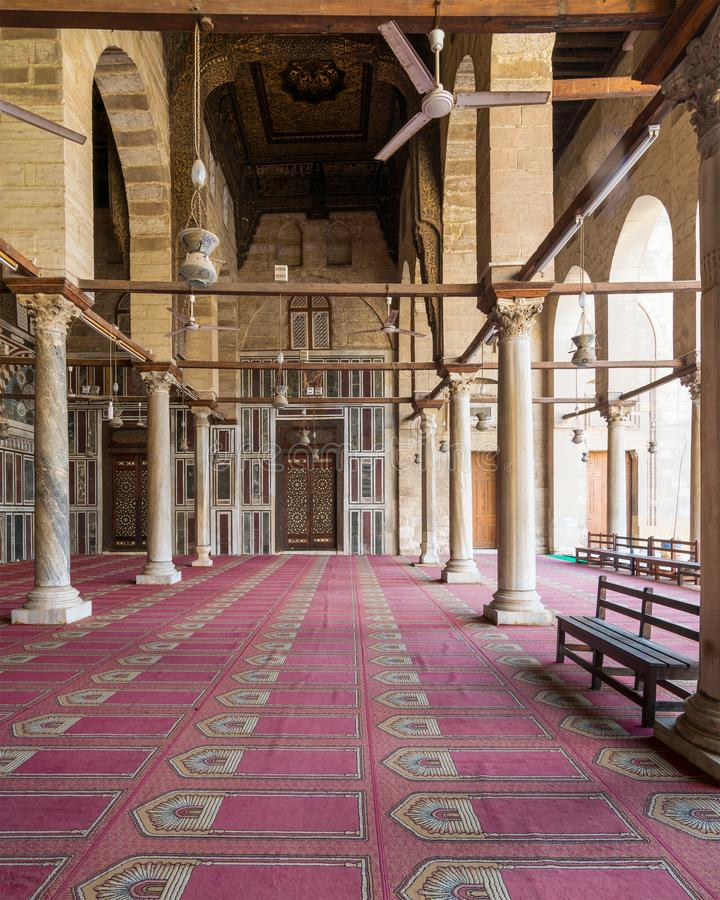 Corridor at mosque of Sultan Moaayad, ending with colorful marble wall and wooden door, Cairo, Egypt. Corridor at public historic mosque of Sultan Al Moaayad stock images