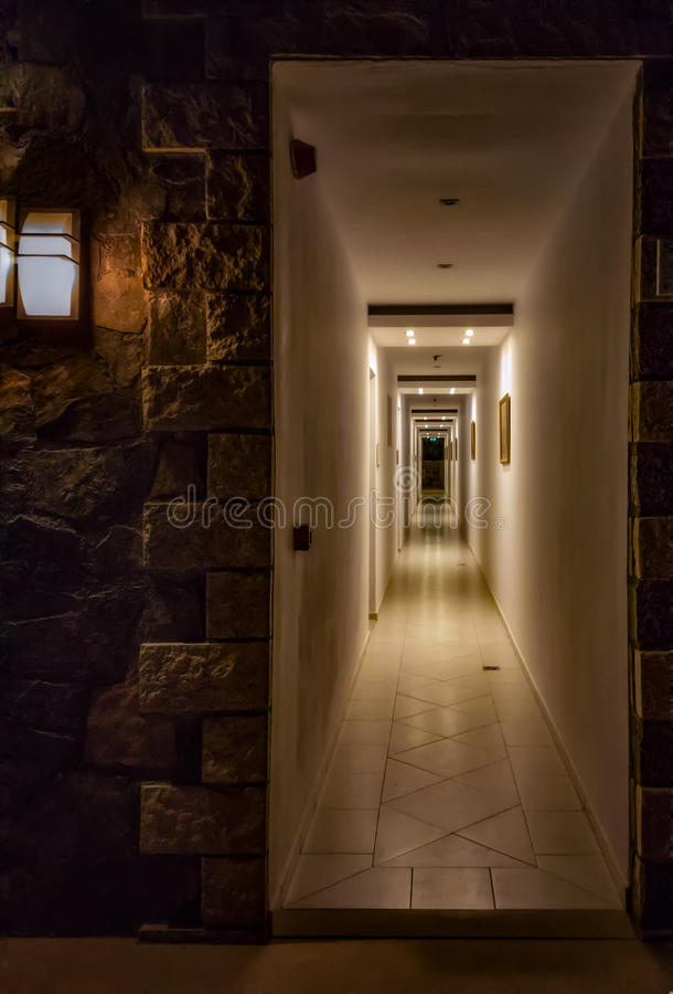 Corridor at night. And entrance to it lighted by lamps stock photos