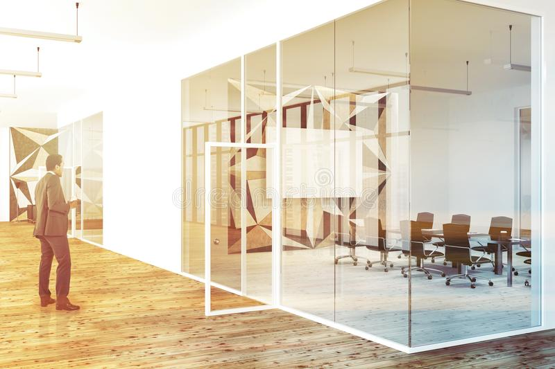 Corridor of a star pattern and glass office man. African American businessman in a star wall pattern office corridor with glass and white walls and a wooden stock photography