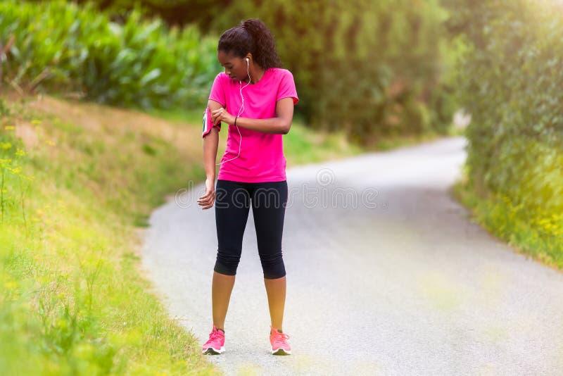Corridore afroamericano della donna che attacca il bracciale di musica - forma fisica immagine stock