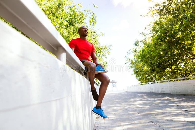 Corridore afroamericano nella città che si siede sul restin del muro di cemento immagini stock libere da diritti