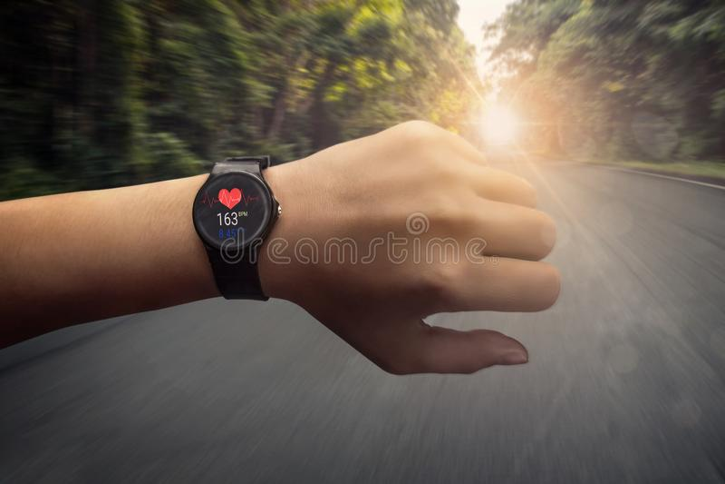 Corridore che controlla al funzionamento astuto dell'orologio del cardiofrequenzimetro su roa immagine stock