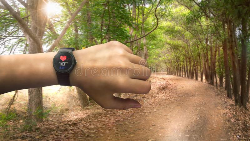 Corridore che controlla all'orologio del cardiofrequenzimetro che corre sulla strada nella f immagini stock