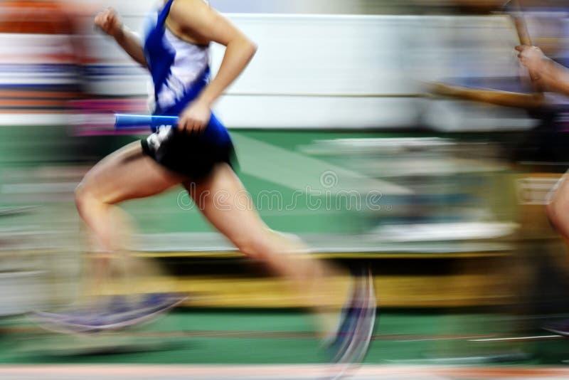 Corridore che esegue una corsa sulla pista con il relè Team Score del bastone fotografia stock libera da diritti