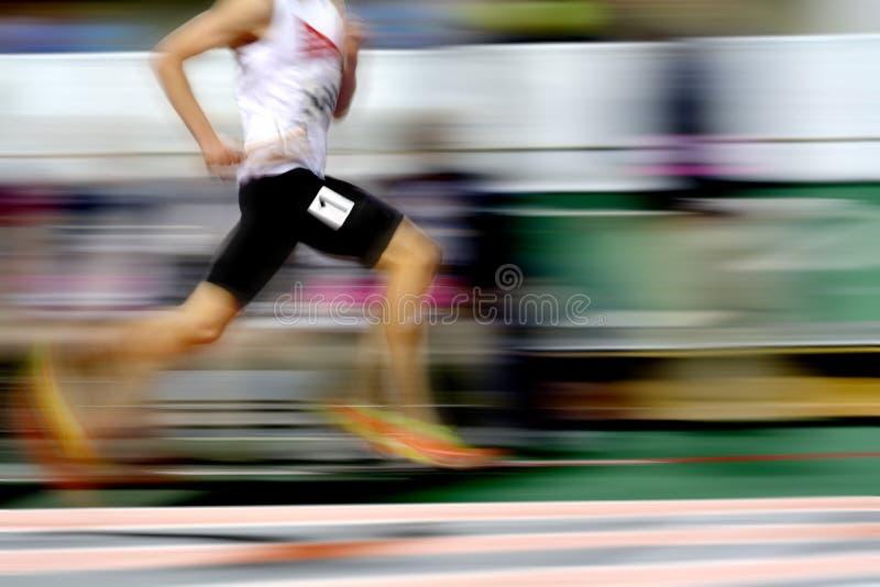 Corridore che esegue una corsa sulla pista con il relè Team Score del bastone immagini stock libere da diritti