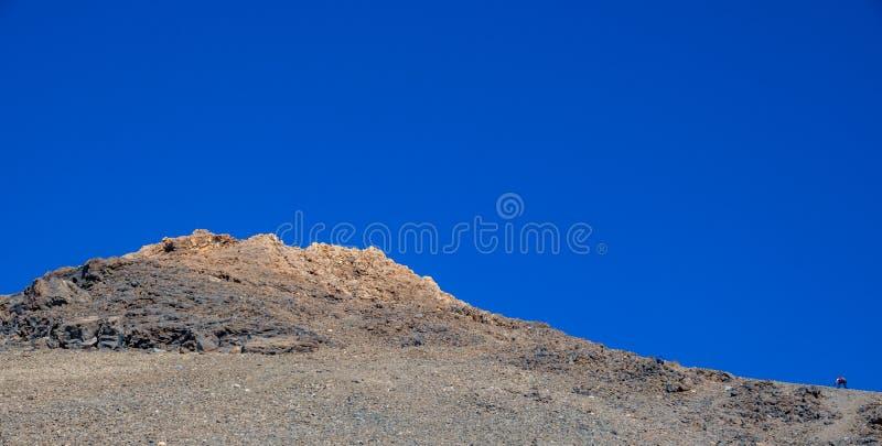 Corridore che scala pendio difficile del vulcano di Teide contro il cielo blu fotografia stock libera da diritti