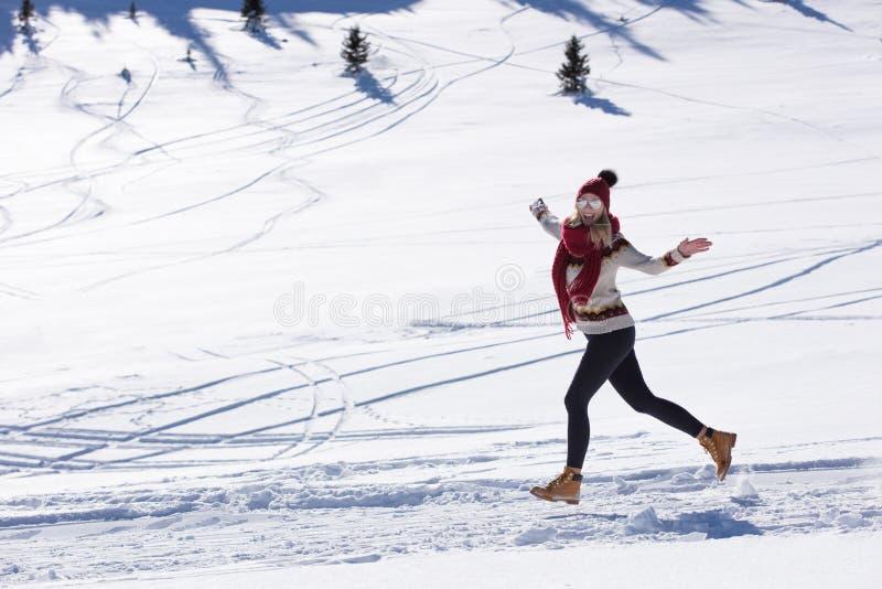 Corridore corrente della donna in montagne di inverno su neve immagine stock libera da diritti