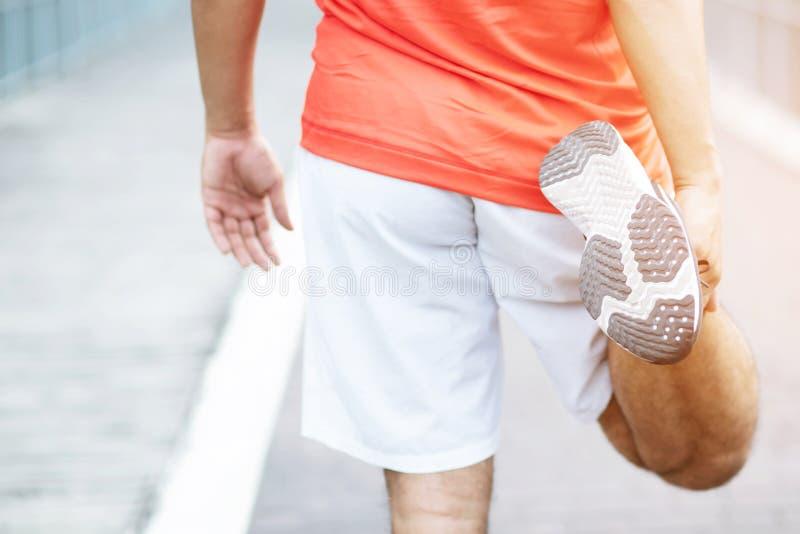 Corridore del giovane che allunga per scaldarsi prima dell'correre o prima di una mattina immagini stock