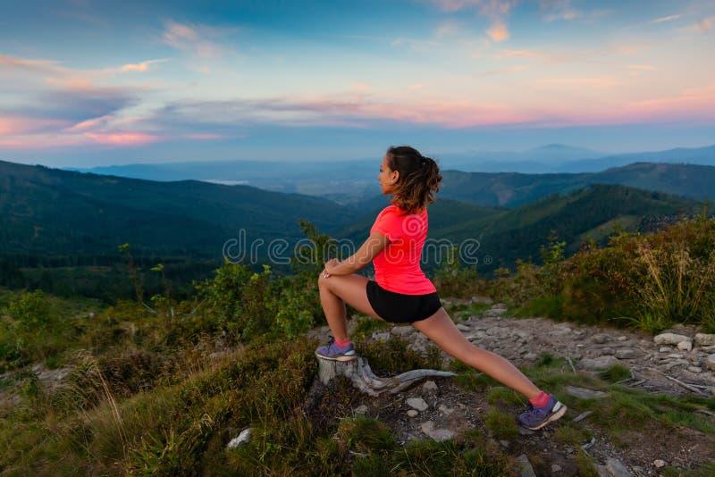 Corridore del paese trasversale della donna che allunga in montagne fotografia stock libera da diritti