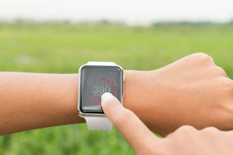 Corridore del primo piano che usando applicazione sana del controllo dell'orologio di Apple fotografia stock libera da diritti
