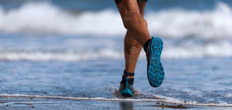 Corridore dell'atleta che corre sulle onde del mare immagine stock