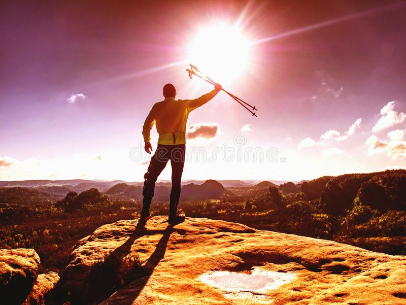 Corridore dell'atleta dell'uomo con i pali di trekking che esegue traccia rocciosa fotografia stock libera da diritti