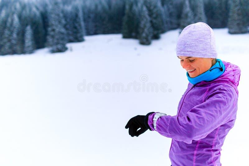 Corridore della donna che controlla orologio sportivo sul funzionamento di inverno immagini stock